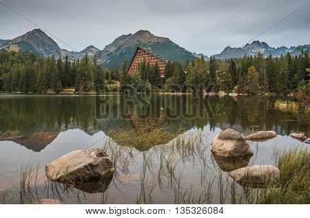 Strbske Pleso Mountain Lake in High Tatras Mountains Slovakia with Rocks and Grass in Foreground in the Rain