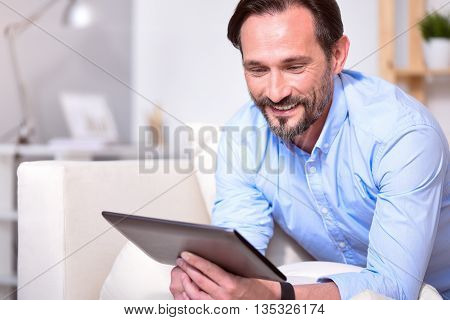 Having a rest. Happy bearded mature man smiling and looking at his tablet while sitting on the sofa