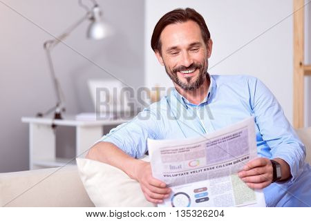 Pleasant article. Joyful bearded middle-aged man reading a newspaper on the couch