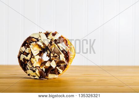 Chocolate donut on a wooden bakery table