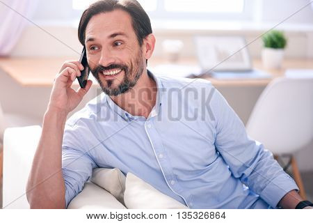 Happy to hear you. Excited middle-aged man having a conversation on the phone while sitting comfortably on the couch
