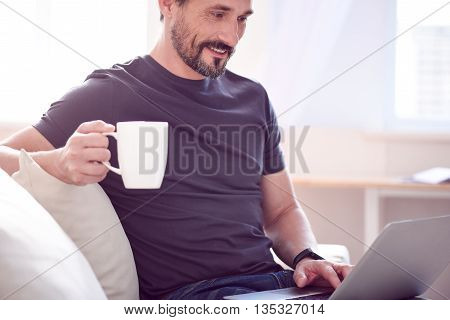 Pleasant time. Relaxed jovial man holding a cup and sitting on the sofa while working on his laptop