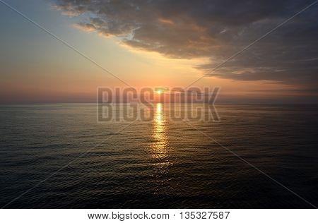 Sunset over calm sea wth dark clouds