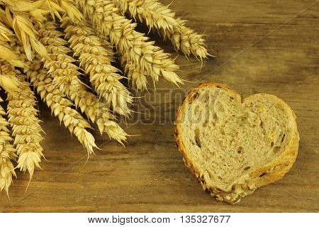 Roll with ears of corn in detail on wooden background