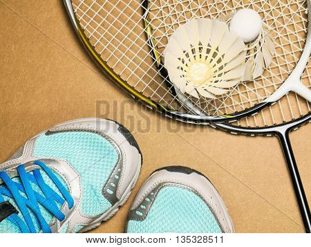 sports set of blue sport shoes and shuttlecocks with two badminton racket on plywood background
