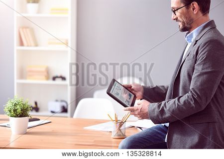 Lets have it done. Elegant bearded mature man with glasses sitting on the table and looking at the tablet with a chart