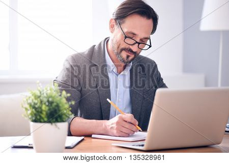 Real professional. Confident satisfied mature man writing in the notebook while sitting at the table in front of the laptop