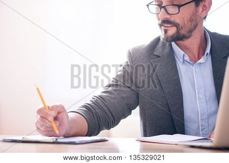 Such a professional. Smiling bearded man with glasses holding a pencil over the papers while working at the table