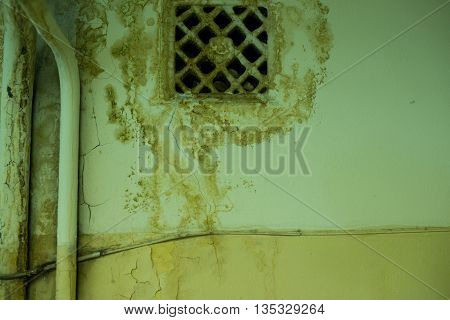 old ventilating lattice and two pipes on the wall with dirty streaked.