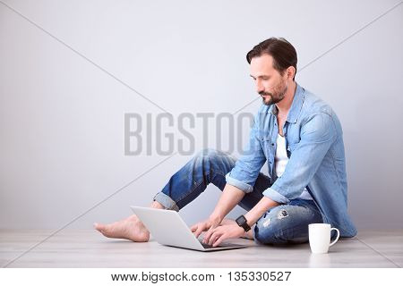Some reflection. Pensive mature bearded man working on the laptop while sitting on the floor on the grey background