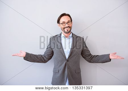 Thats it. Contented bearded middle aged man holding arms wide open while standing isolated on the grey background