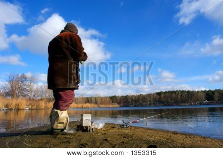 A Fisherman Looks After A Rod On The Shore