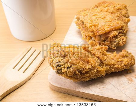 fried chicken on a chopping broad with a glass set on a wood background