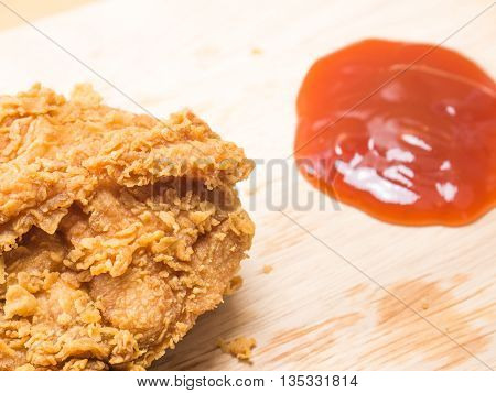 close up fried chicken on a chopping broad with a tomato sause set on a wood background