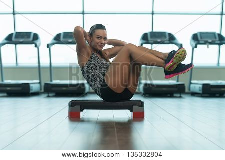Young Woman Doing Abdominal Exercise On Stepper