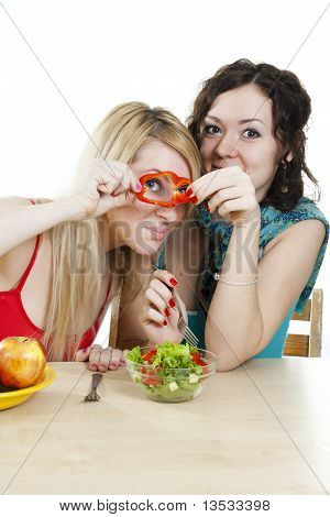 Girlfriends Cheerfully Play With Meal Behind A Table