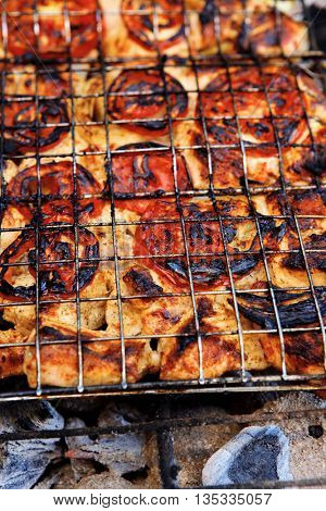 grilling spiced chicken in grid on charcoal bbq with tomatoes and vegetables