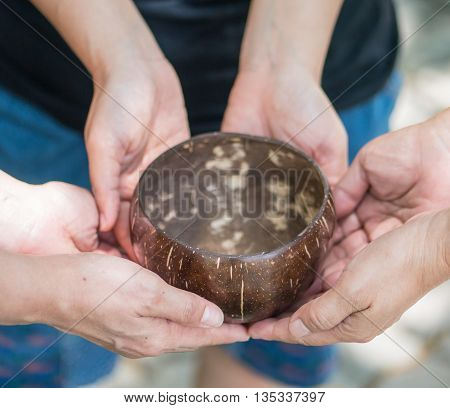 Coconut bowl on hands, concept ask for