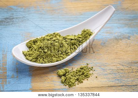 white spoon of organic matcha green tea powder against grunge wood