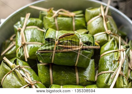 Steamed sticky rice and banana wrapped in banana leaves. Traditional Thai food style,