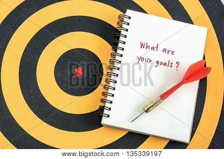 Handwriting what are your goals in notebook with dart target over dartboard Business success concept
