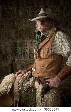 Old west cowboy with woolie chaps, pistols, vest and cowboy hat