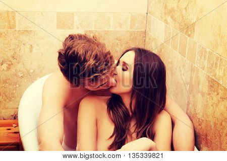 Beautiful young couple kissing in a bath.