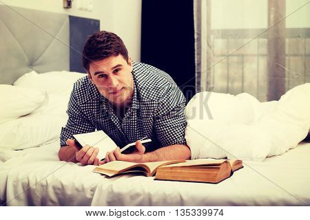 Thoughtful man with a book in his bed.
