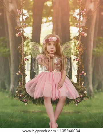 A little girl is sitting in the woods on a swing with sparkle fairy wings blowing magical dust for an imagination or fairy tale concept.