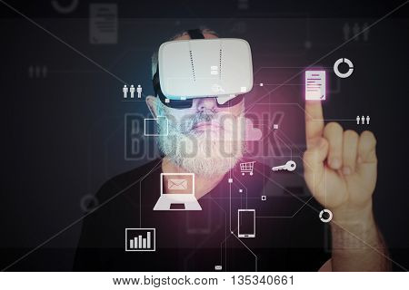 Aged bearded man in 3d virtual reality glasses over dark background is clicking on white virtual icon