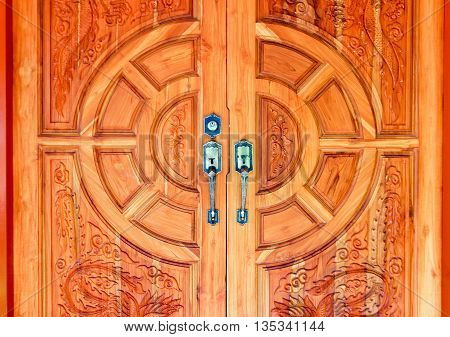 wooden door decorated with modern style metallic door handle on wooden door