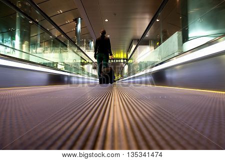 Young girl in the airport walking on a flight