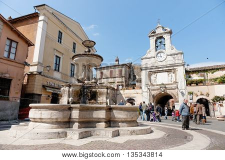 Sutri, Italy - April 17, 2011; Small Italian village square with people gathering and traditional fountain clock tower and arched entry in historic Mediterranean town.