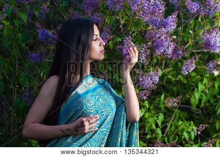 Woman wearing traditional sari with mehndi in lilac bushes
