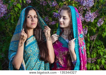 Asian women dressed in traditional saris with mehndi in lilac