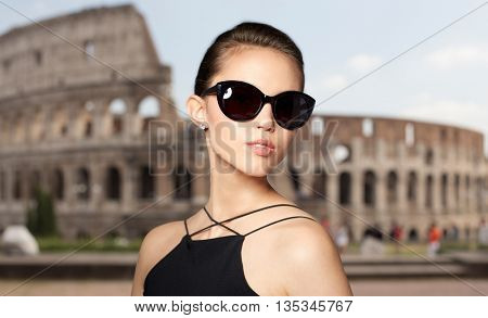 accessories, eyewear, fashion, people and luxury concept - beautiful young woman in elegant black sunglasses over coliseum background