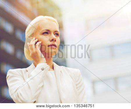 business, technology and people concept - serious businesswoman with smartphone talking over office building