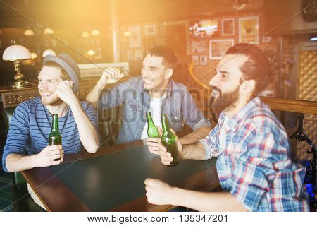 people, leisure, friendship and bachelor party concept - happy male friends drinking bottled beer and raised hands rooting for football match at bar or pub