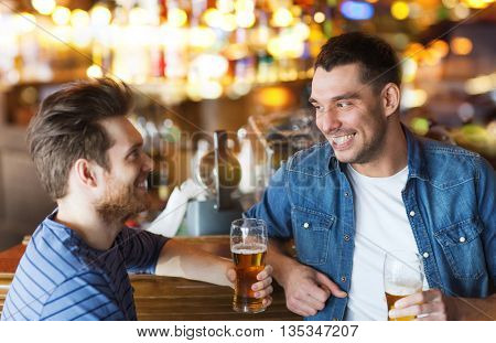 people, men, leisure, friendship and communication concept - happy male friends drinking beer and talking at bar or pub