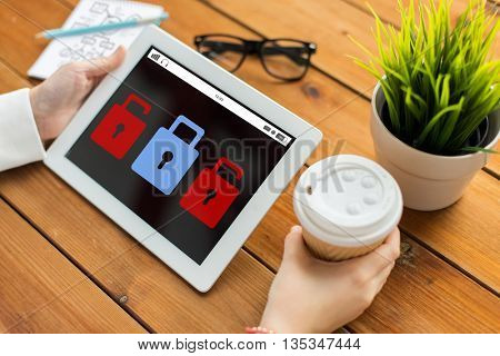 business, technology, people, cyber defense n and security concept - close up of woman with lock icon on tablet pc computer screen and coffee cup on wooden table