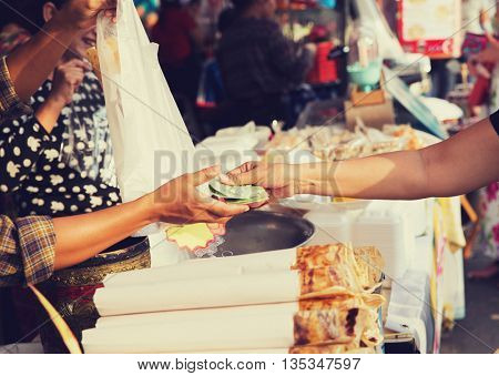 sale, retale, shopping and food concept - close up of hands giving money at street market
