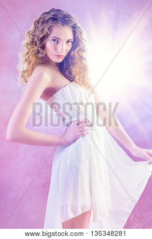 Beautiful romantic girl with wavy hair in light white dress over pink background. Spring look. Natural make-up.