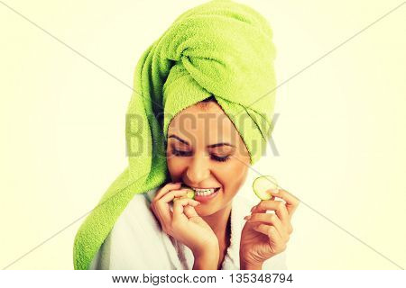 Woman in bathrobe eating cucumber
