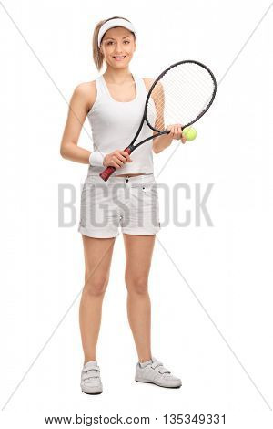 Full length vertical shot of a female tennis player posing with a ball and a racquet isolated on white background