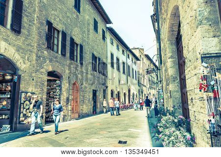 San Gimignano, Italy - April 18, 2011; Old image faded colors effect of tourists in in narrow street Italian Tuscan walled city of San Gimignano