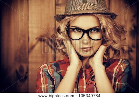 Pretty hipster girl in hat and glasses posing by a wooden wall. Youth style, fashion.