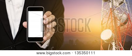 Mobile phone in businessman's hand, with satellite dish telecom network on telecommunication tower at sunrise