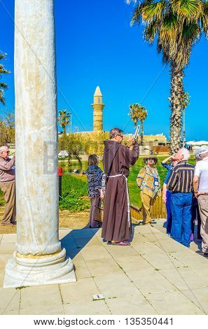 CAESARIA ISRAEL - MAY 19 2016: The group of tourists with the franciscan monk guide in the open air museum on May 19 in Caesaria.