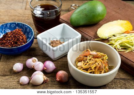Food series : Spicy and sour mangoes salad with ingredients on wooden plank table, Thai food