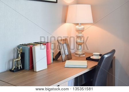 Wooden Table With Reading Lamp And Books In Modern Working Room Interior